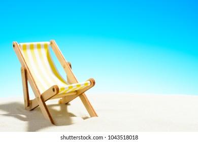 Sun lounger on the sandy beach, sky with copy space