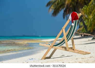 Sun lounger with Santa hat at beautiful tropical beach with white sand and turquoise water, perfect Christmas vacation