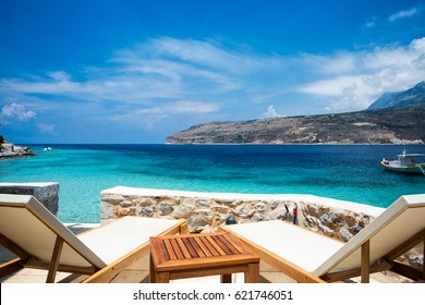 Sun lounger and umbrella on the mediterranean sea. Vacation concept in Peloponnese, Greece