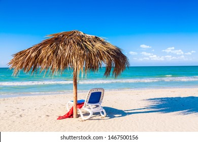 A sun lounger under an umbrella on the sandy beach by the sea and sky. Vacation background. Idyllic beach landscape.