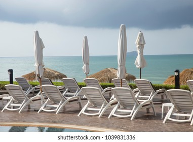 Sun loungers and closed umbrellas front on the beach