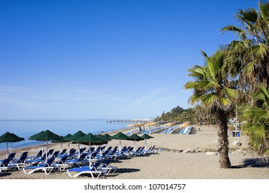 Sun loungers on a beach at the popular resort of Marbella in Spain, Costa del Sol, Andalusia