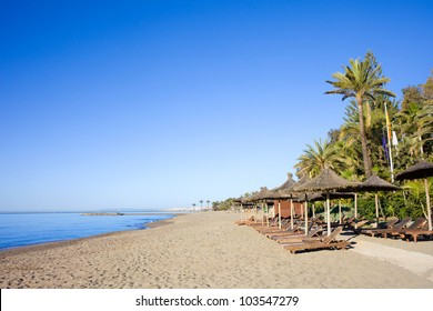 Sun loungers on a sandy beach by the Mediterranean Sea at the popular resort of Marbella in southern Spain, Costa del Sol, Andalusia region, Malaga province.
