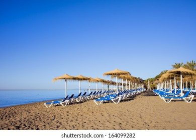 Sun loungers on a tranquil beach at the popular resort city of Marbella in Spain, Costa del Sol, Malaga province.