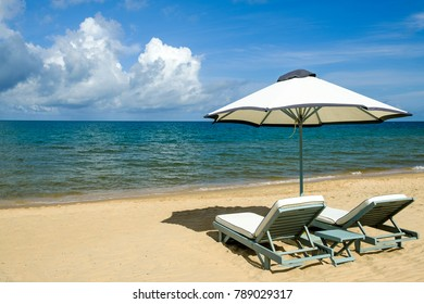 Sun Loungers and parasol on an empty beach facing the sea.