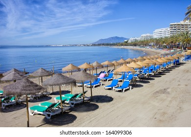 Sun loungers and straw shade umbrellas on a beach by the Mediterranean Sea in Marbella, Costa del Sol, Spain.