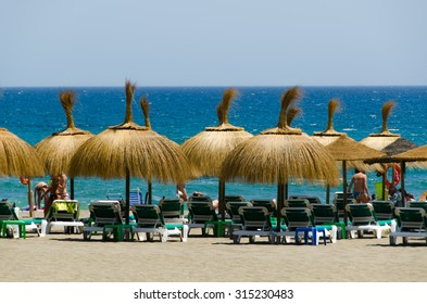 Sun loungers and straw shade umbrellas on a beach by the Mediterranean Sea in Marbella, Costa del, Spain on July 2015.