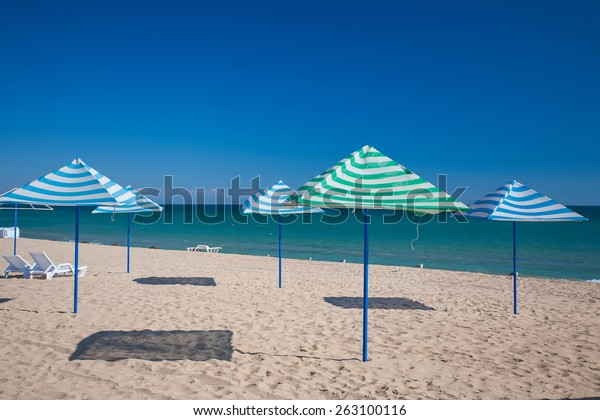 Sun loungers and straw shade umbrellas on a beach
