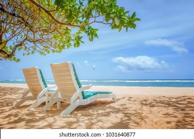 The sun loungers under the trees on a tropical beach. Ocean view, Nusa Dua, Bali, Indonesia.