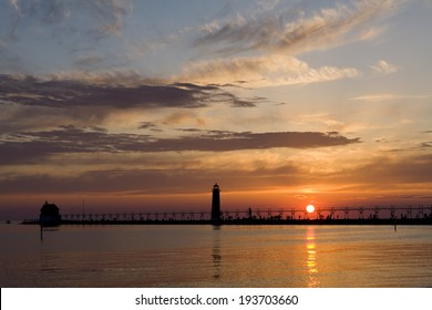 The sun makes a perfect ball of light as it sets over Lake Michigan behind the Grand Haven Pierhead Light, Grand Haven, MI