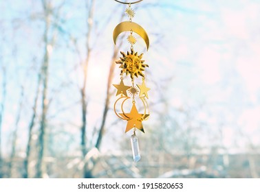 sun and moon golden amulet on abstract natural background. symbol of spring equinox, winter solstice. winter or spring season
