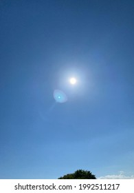 The sun on a clear blue sky with some lens flare. - Shutterstock ID 1992511217