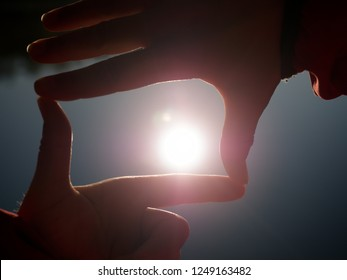 Sun on female hand. Silhouette of hand holding sun. Sun low above water level. Lovely shadow play.