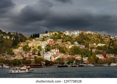 Sun on homes on a hillside of Arnavutkoy Besiktas Istanbul with storm clouds on the Bosphorus Strait, Besiktas, Turkey - November 14, 2012