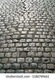 The sun on some cobbles of an old cracked and uneven London street