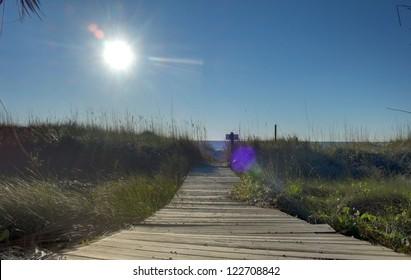 The sun on a wooden walkway to the Atlantic Ocean near a luxury beach house in Hilton Head, SC.