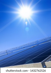 Sun over blue solar panel. Renewable, alternative solar energy, sun-power plant on sky background.