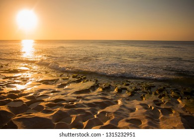 Sun over exotic Balangan beach shore. Sunset view. Bali. Indonesia. Close-up sunlit sand boulders. Amazing Balinese Martian landscape. Ideal background for the collages and illustrations.
