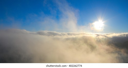 sun over fog and clouds