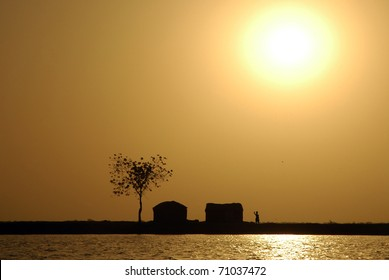 Sun over traditional West African huts along the Niger river shore