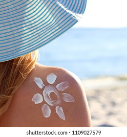 sun painted with sunscreen on a girl's shoulder against the sea
