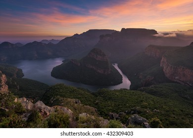 The sun paints high clouds in oranges over the Blyde River Canyon at sunrise