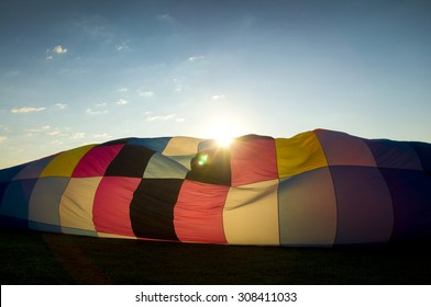 Sun peaking over the inflating envelope of a hot-air balloon