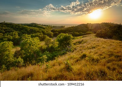 Sun peaking under clouds at sunset over rolling hills