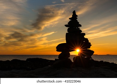 The sun peaks through a cairn of rocks along the coast of New England.