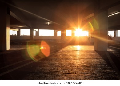 Sun peeking into large dark empty grunge parking structure industrial interior.