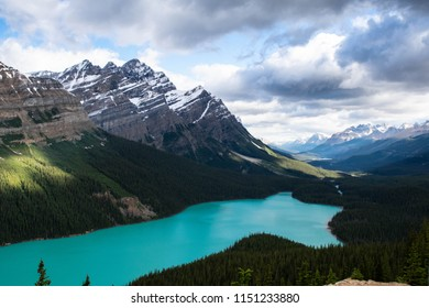 Sun peeking through the clouds at Peyto Lake, Banff, Alberta. Sun spots tickle the mountaintops