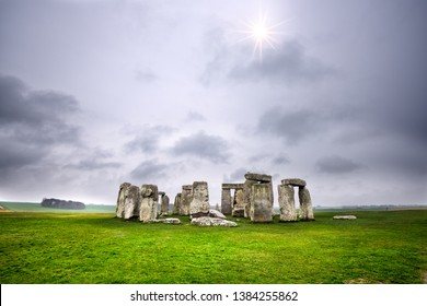 Sun piercing through the clouds at Stonehenge, England
