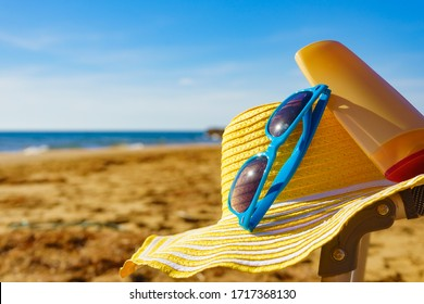 Sun protection accessories on sea shore. Blue sunglasses, yellow straw hat and sunscreen lotion on sandy beach. Summer and holidays.