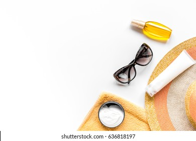 Sun protection composition with glasses and cream on white background top view mockup