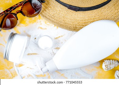 Sun protection cosmetic cream with beach outfit on orange backgr
