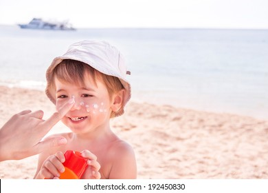 Sun protection. Hand of caucasian mother applying suncream  (suntan lotion) from a plastic container to her happy son before tanning during summer holiday on beach.  Copyspace, close up.