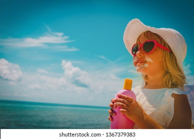 sun protection - happy little girl with suncream at beach