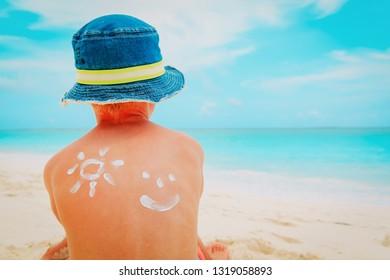 sun protection- little boy with suncream at tropical beach