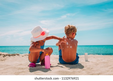sun protection, little girl applying sunblock cream on boy shoulder