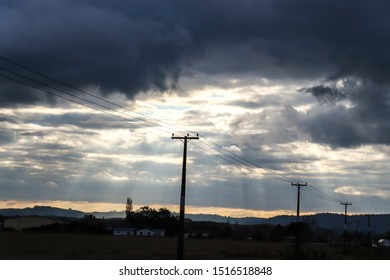Sun ray in power pole in a cloudy sky in new zealand. Image of Crepuscular Ray with power poles.