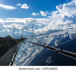 Sun rays beam down onto solar power energy panels with electricity pylons in background