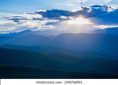 Sun rays beaming though the clouds across tree covered mountains
