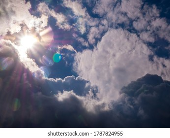 Sun with rays in the blue sky and thick clouds