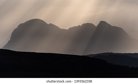 Sun rays, also called crepuscular rays, streaming through gaps in clouds above the iconic mountian of Suilven in Assynt in the far north of Scotland