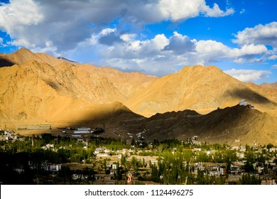 Sun rays getting filtered by the clouds in the sky and casting a shade on the mighty mountains in Leh, India.