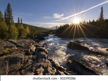 Sun with sun rays giving golden glow to river landscape