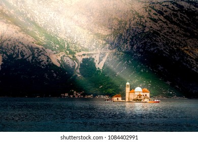 Sun rays illuminate the island at Boka Kotor bay (Boka Kotorska), Montenegro, Europe