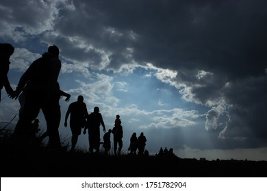 Sun rays illuminate people. Immigration of people. Blue sky with dark clouds