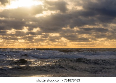 The sun and the rays of the sun make their way through the clouds to the stormy sea