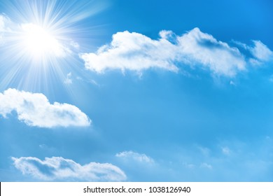 Sun with sun rays on the blue sky with clouds